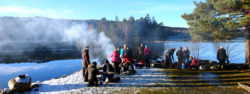 Matlagning kring elden vid spegelblankt vatten